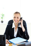 Self-assured businesswoman talking on phone. In her office sitting at her desk Stock Photo