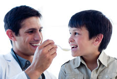 Self-assured doctor giving medicine to a boy Stock Image