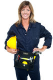 Self assured female architect holding hard hat Royalty Free Stock Images