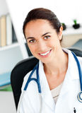 Self-assured female doctor smiling at the camera. Sitting in her practice Royalty Free Stock Images