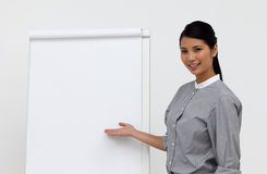 Self-assured female executive pointing at a board Stock Photography