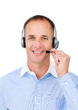 Self-assured mature businessman using headset. Against a white background Royalty Free Stock Image
