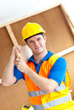Self-assured young male worker carrying a board Royalty Free Stock Photos