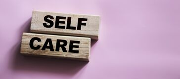 Self care words on wooden blocks, self treatment concept, pink background