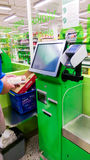 Self-checkout made by a male customer in a finnish supermarket. In Tampere, Finland- the man is scanning the groceries and pays with the card, the metal Royalty Free Stock Photo