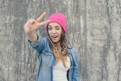 Self-confidence concept. Happy smiling winking and flirting woman dressed in casual clothes and pink hat showing v-sign against s royalty free stock images
