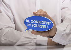 Self Confidence. Image of a man hand holding blue speech balloon with the text be confident in yourself, white shirt and reflexion. Concept and motivation for Stock Photography