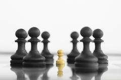 Self confidence white peon standing in front of a black chess ar. My before confrontation Royalty Free Stock Image