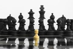 Self confidence white peon standing in front of a black chess ar royalty free stock image