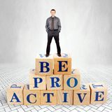 Self Confident man stands on the top of heap of wooden blocks with a call Be Proactive royalty free stock photography