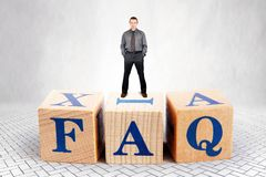 Self Confident man stands on the top of heap of wooden blocks with letters FAQ royalty free stock photos