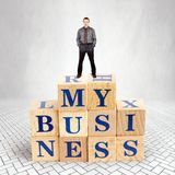 Self Confident man stands on the top of heap of wooden blocks with a text My Business royalty free stock photo
