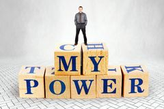 Self Confident man stands on the top of heap of wooden blocks with a text My Power stock images