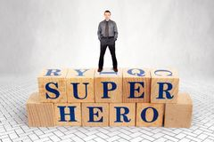 Self Confident man stands on the top of heap of wooden blocks with a text Super Hero royalty free stock image