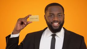 Self-confident afro-american man in formal suit presenting gold card advertising. Stock footage stock footage