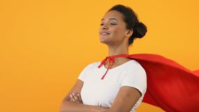 Self-confident afro-american woman with crossed hands in red cape, super hero