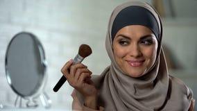 Self-confident arab lady doing make-up, applying powder by brush, femininity. Stock photo royalty free stock images