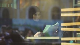 Self-confident Arabic business lady in cafe looking through documents, freedom. Stock footage stock video footage