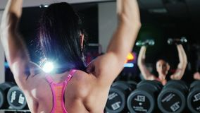 Self-confident athletic woman is engaged in a sports hall. Trains with a dumbbell. Slow motion stock footage