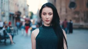Self-confident attractive young girl with natural makeup in a black outfit looks right towards the camera and walks down stock video