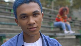 Self-confident blue-haired black teen guy smiling on camera, adolescence age stock video