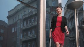 Self-confident business woman in a red dress walks against the backdrop of modern buildings. portrait of a young woman