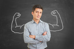Self confident businessman with chalk muscles. Strong and self confident businessman with chalk muscles on blackboard behind him stock photo