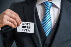 Self-confident businessman in suit is showing label that he is the best boss ever Stock Image