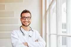Self-confident doctor smiling. Self-confident competent doctor friendly smiling Royalty Free Stock Image