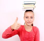 Self-confident girl with OK signand  books on head Stock Photo