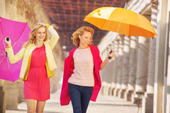 Self-confident girls walking with umbrellas Royalty Free Stock Image