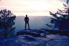 Self confident hiker in akkimbo pose on the peak of rock royalty free stock images
