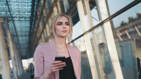 Self-confident hot young blonde girl walks by the business centre, uses her cell phone. Stylish look, elegant white stock footage