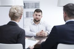 Self-confident man during job interview. Self-confident men listening to recruiters during a job interview in corporation Royalty Free Stock Photo