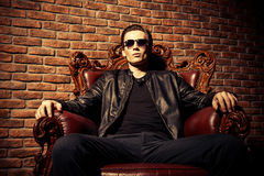 Self-confident man. Portrait of a brutal confident young man sitting relaxed in expensive vintage armchair. Mafia, criminal concept stock images