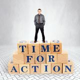 Self Confident man stands on the top of heap of wooden blocks with a call Time For Action stock image