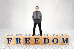 Self confident man stands on wooden blocks with a word Freedom stock photos