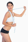 Self confident slim woman playing with her measuring tape Stock Images