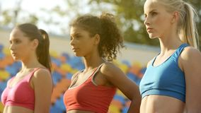 Self-confident sportswomen seeing strong competitors in each other, sports team royalty free stock image