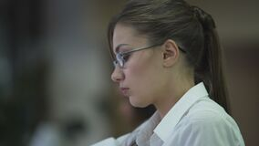 Self-confident successful young lady working on project, using laptop at office. Stock footage stock video