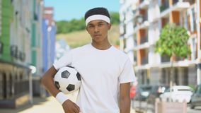 Self-confident teenage football player with ball looking on camera, challenge stock video footage