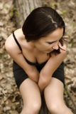 Self-conscious girl sitting on a log. In forest Stock Image