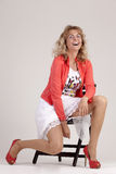 Self-conscious woman. In summer outfit on a chair laughing Royalty Free Stock Images