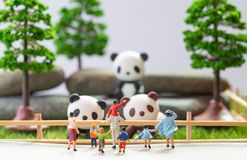 A self constructed miniature toys concept of people at the zoo - school kids and family watch pandas.  stock photography