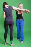 Self defence classes. Women self defence classes - exercises on green background Royalty Free Stock Photography