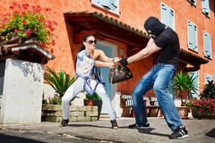 Self defence in the street. Good looking pretty women defending herself kicking a mugger between the legs who trying to steal her bag in the street stock images
