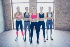 Self defend class concept. Full length photo of five  young spor. Tive girls, standing with crossed hands in the gym, serious and ready for difficult work out Royalty Free Stock Images