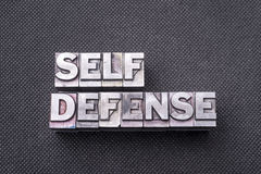 Self defense bm. Self defense phrase made from metallic letterpress blocks on black perforated surface Royalty Free Stock Images