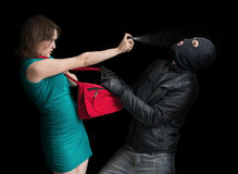 Self defense concept. Young couple is defending with pepper spray. Self defense concept. Young couple is defending with pepper spray against thief in balaclava Stock Photos