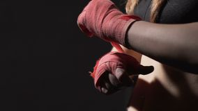 Self-defense course, strong woman Muay Thai boxer wrapping bandage on her hand